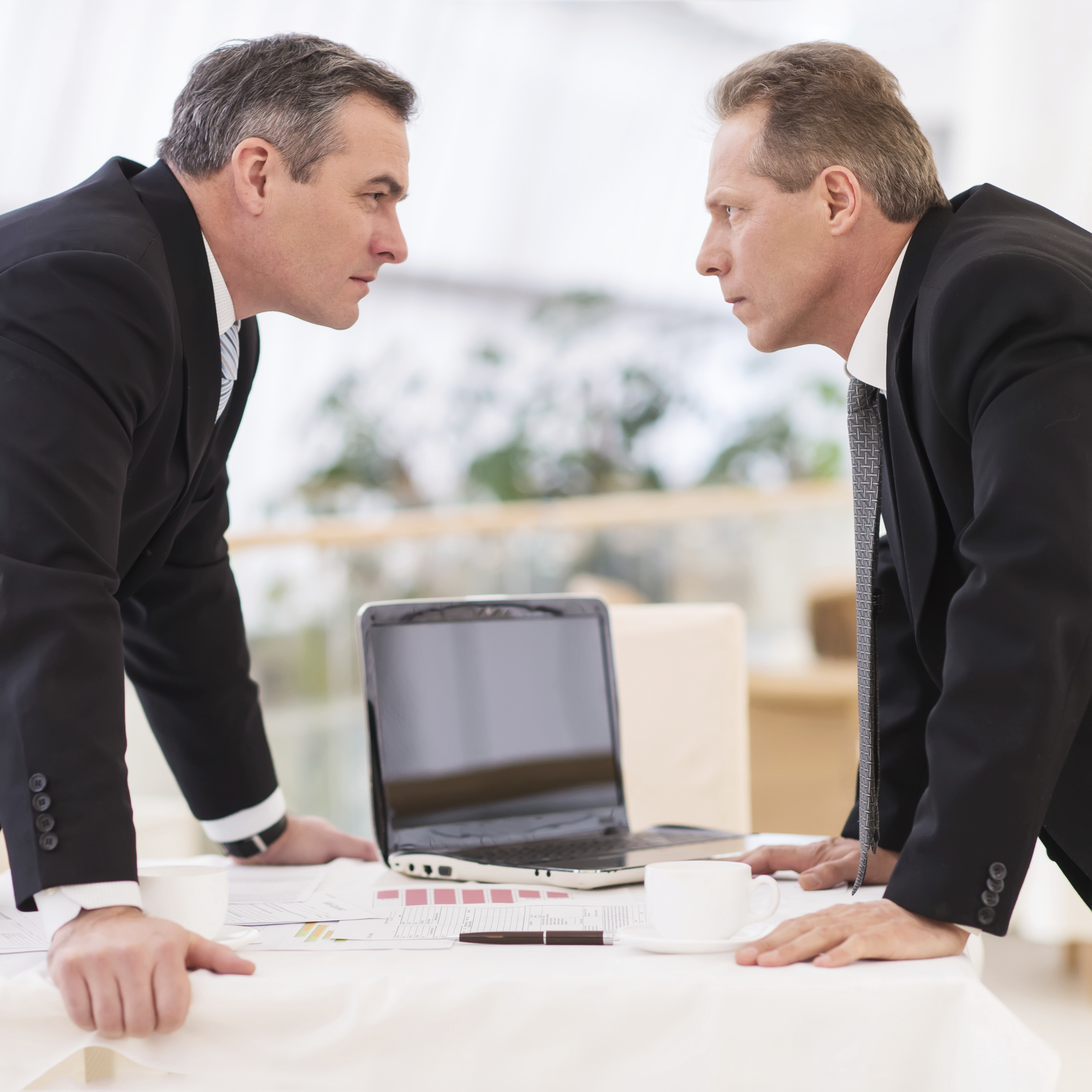 Business confrontation. Two mature men in formalwear conflicting while standing face to face
